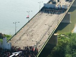 Demonstrators cross the first barrier of Al-Jumhuriya Bridge in Tahrir Square in Baghdad