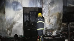 Civil defense teams put out fires that broke out inside a building in Najaf