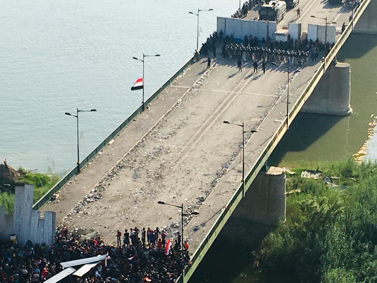 المتظاهرون يعبرون الحاجز الاول من جسر الجمهورية بساحة التحرير في بغداد